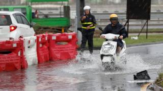 澳門一名男子騎著摩托車開過略有積水的馬路(27/8/2017)