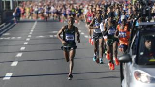 Shura Kitata, left, and Lelisa Desisa, right, run.