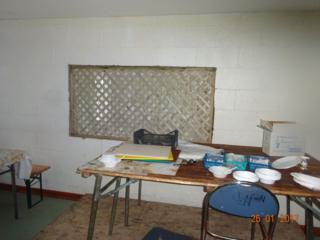 Messy looking desk in scruffy room, photographed by Ofsted in unregistered school