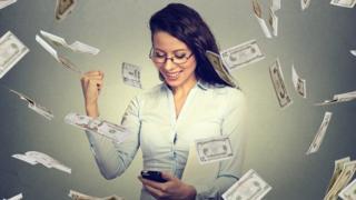 Mujer con teléfono móvil rodeada de billetes de dólares