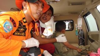 Rescuers with a young survivor, 20 Dec