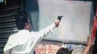 A man believed to be Raja Chauhan pointing his pistol in a photo that has gone viral