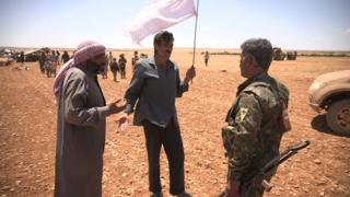 Kurdish fighter talking to displaced civilians in countryside outside Manbij