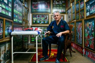 A man sits amongst football memorabilia