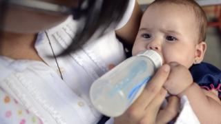Una madre da el biberón a un bebé