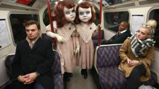 two Victorian dolls travelling on the London Underground as passengers watch on