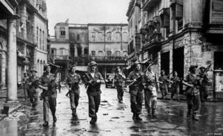 British troops in Calcutta, with rifles at the ready, clearing a street after Hindus and Muslims used firearms against each other. (Pho