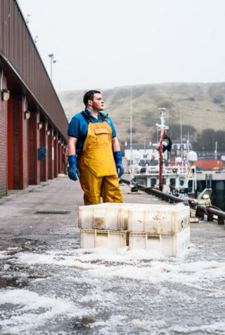 A fisherman stands on shore with ice and boxes