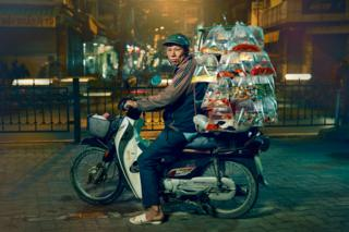 A man is posed on a motorcycle with an array of multicoloured fish in plastic bags hanging in rows on the back of the bike