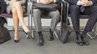 Piernas de personas sentadas esperando su turno para una entrevista de trabajo