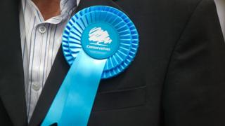 A man wearing a Conservative rosette