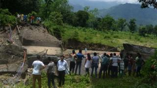 Bystanders look at a damaged bridge in the village of Garidhura some 35kms from Siliguri on July 1, 2015, after landslides struck the eastern state of West Bengal