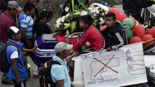 "Colombian indigenous people hold a sign reading: ""Let not the weapons silence us"" during the funeral of Kevin Mestizo and Eugenio Tenorio,"