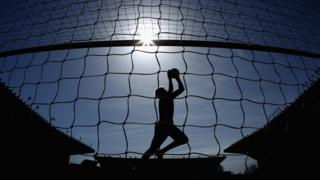 A football goalkeeper in silhouette