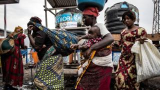 Women wash their hands at an Ebola screening station as they enter DR Congo from Rwanda