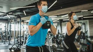 Man and woman wearing masks working out at a gym