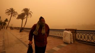 A man covers his face during a sandstorm near the River Nile in Cairo, Egypt, 16 January 201