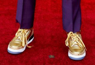 Золоті кросівки на червоній доріжці