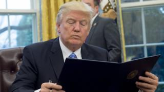 US President Donald Trump reads an executive order withdrawing the US from the Trans-Pacific Partnership prior to signing it in the Oval Office of the White House in Washington, DC, January 23, 2017