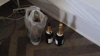 Bottles of champagne sit next to a bed where the intruder was arrested