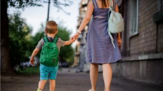 Woman and boy walk away holding hands