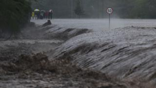 """People watch as flash floods rage past a part of the main highway to Kenya""""s border town with Tanzania on March 15, 2018 in Isinya, Kajiado county, around 58 kilometres (36 miles) southeast of capital Nairobi."""