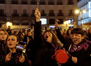 Women bang pots and pans during a protest