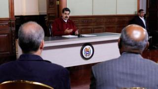 Nicolás Maduro fala em reunião observado por outras pessoas no Palácio Miraflores