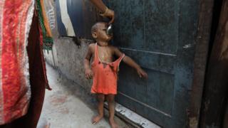 一个逃到印度德里的罗兴亚难民妈妈在喂孩子食物