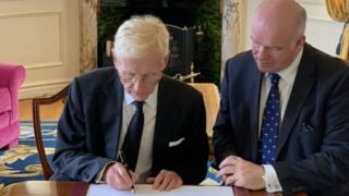 Lt Governor Sir Richard Gozney signing the revocation watched by chief minister Howard Quayle