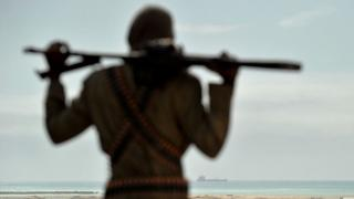 Mohamed Garfanji, Somalia's top pirate boss, stands on sandy dunes just outside the central Somali coastal town of Hobyo as he watches the outline of a hijacked ship anchored off the coast on August 20, 2010