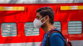 A man wearing a face mask walks past an Indian Railway train coach which is being set up for isolation