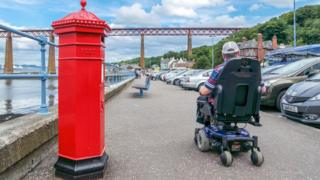 Man in wheelchair next to Forth Bridge