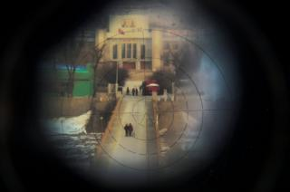 Women, photographed from the Chinese side of the border, are seen through binoculars.
