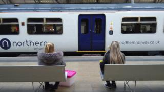 women sit on platform looking at northern railway train