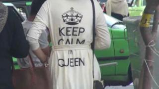 "A video report by Iran's Fars news agency shows a woman with a top bearing the slogan ""Keep calm, I'm queen""."