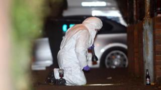 Forensic detective examines scene of shooting