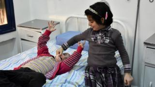 Syrian girls who had been held prisoner by rebel forces await treatment at a hospital in Aleppo following their release as part of a prisoner swap (12 April 2017)