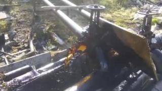 A still of oil gushing from a leaking pipe in Chersky