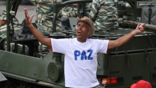 """Un partidario del gobierno chavista en Venezuela con una camiseta con la palabra """"paz"""", frente a un vehículo con soldados."""