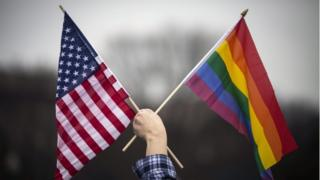 American and Pride flags held up