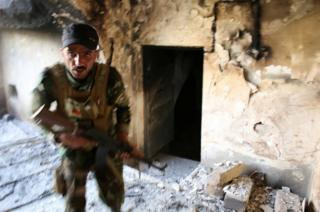 A Kurdish Peshmerga fighter searches a house for Islamic State militants in Tel Asqof, northern Iraq