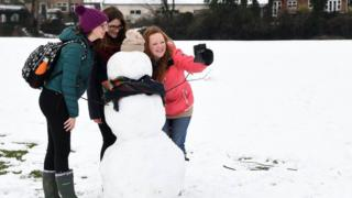 Woman take a selfie with a snowman in High Wycombe, Buckinghamshire.