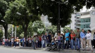 People queue to try to buy basic food items outside a supermarket in Caracas, Venezuela, April 28, 2016