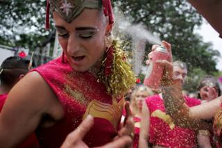 Glitter is sprinkled on a male participant in make-up, who turns his face from an accompanying adhesive spray, during the annual Sydney Gay and Lesbian Mardi Gras festival in Sydney, Australia March 4, 2017.