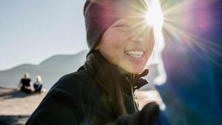 Moça numa montanha sorri