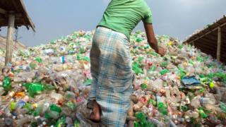 Hombre sobre montaña de botellas de plástico.