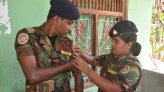 Gauri adjusts a badge on Roshan's uniform