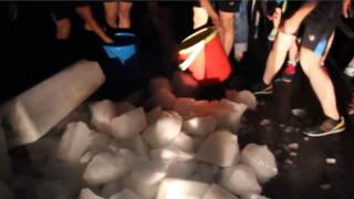 Students collecting ice into buckets at Lushan College in the Chinese city of Liuzhou.