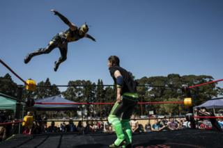 A masked wrestler leaps at his opponent from the corner of the ring.